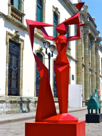 Red geometric sculpture of woman