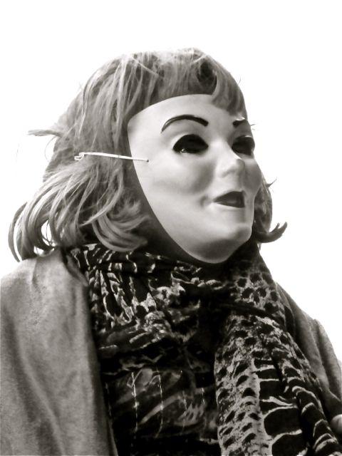Man wearing female mask, wig, and clothing