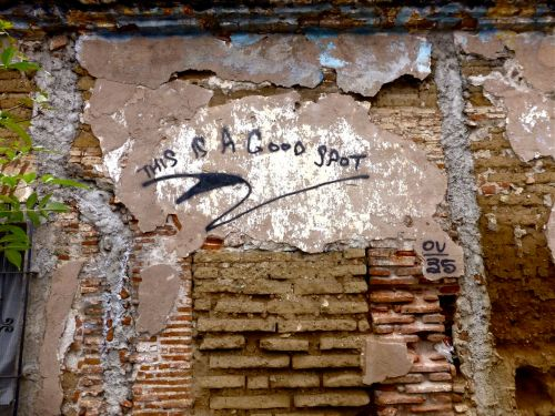"Crumbling adoble & brick wall with graffiti, ""This is a good spot"""