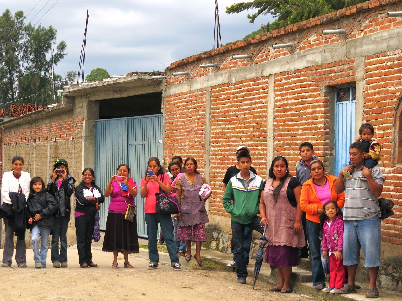 Men, women, and children standing on street