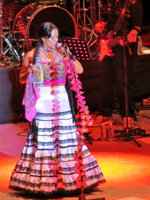Lila Downs with bottle of mezcal
