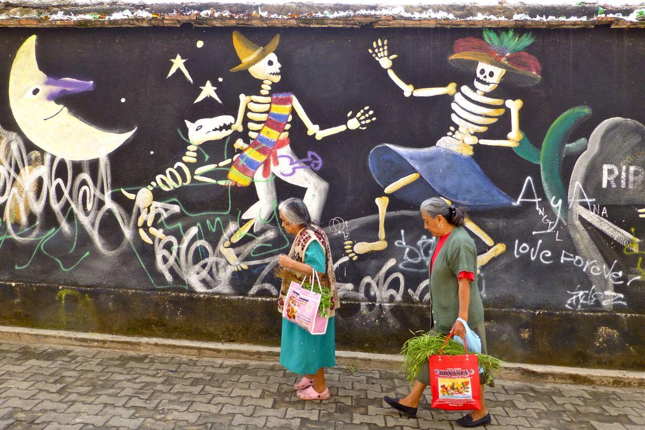 2 women in front of mural with2 dancing skeletons