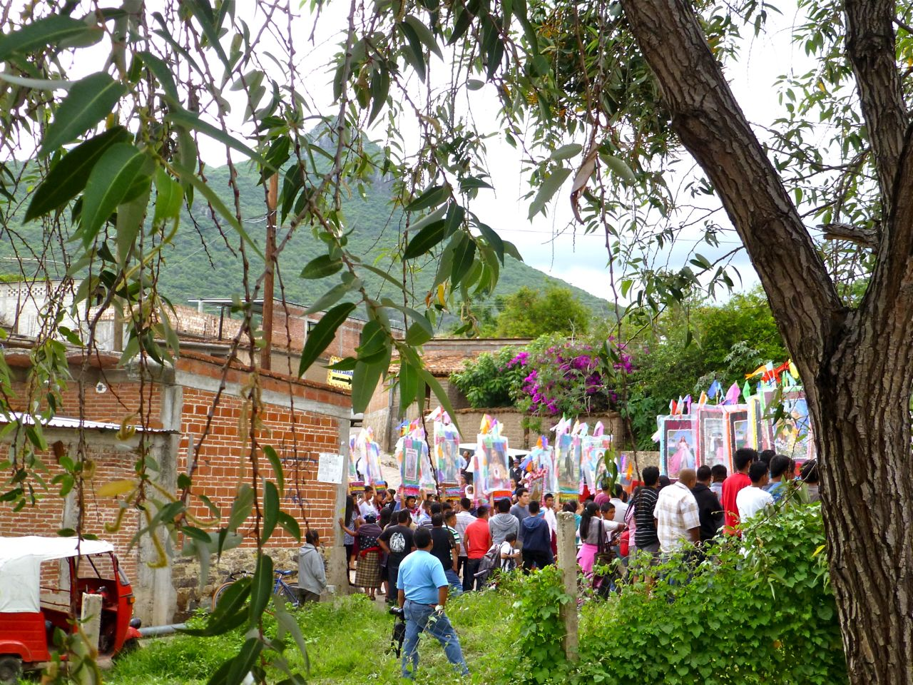 Procession in mid-ground and mountain in background