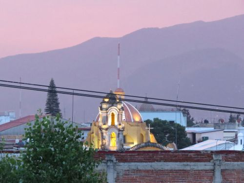 Pink tinged mountains & sky with church in foreground