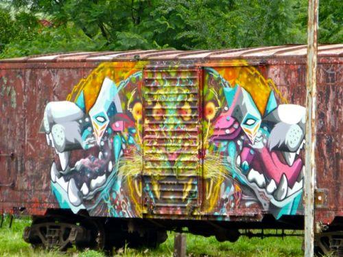 3 creature faces big teeth painted on railroad car
