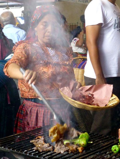 Woman at grill behind smoke