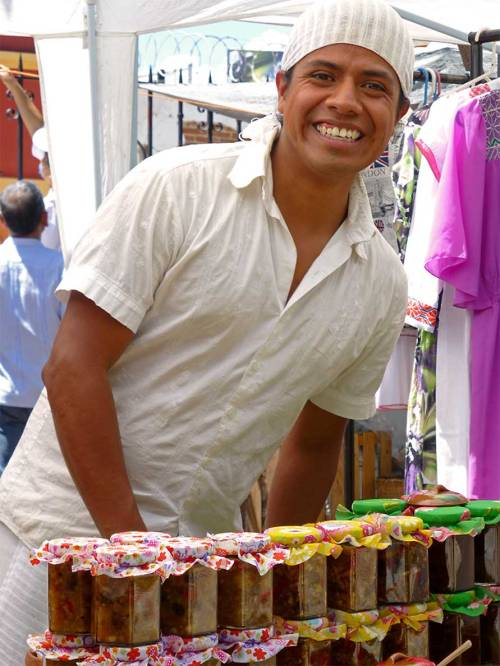 Smiling young man selling jars of chutney
