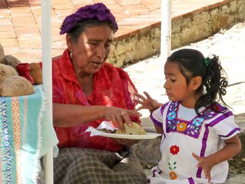 A grandmother and little girl sharing plate of food