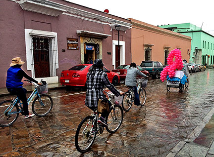 Bike riders on wet cobblestone street