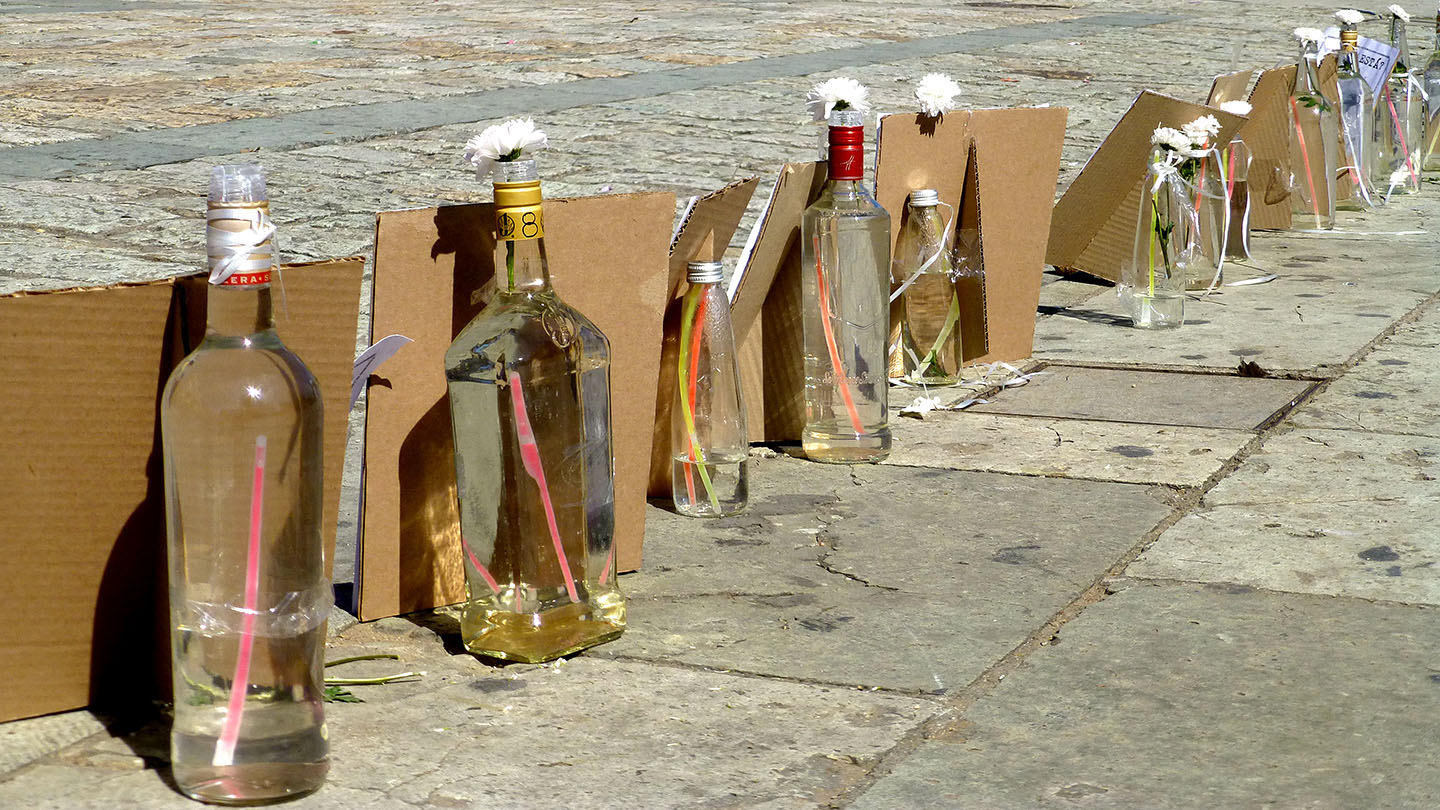 Bottles with flowers propping up cardboard