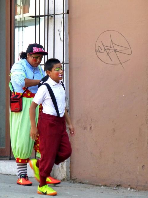 Female & boy clown walking down street