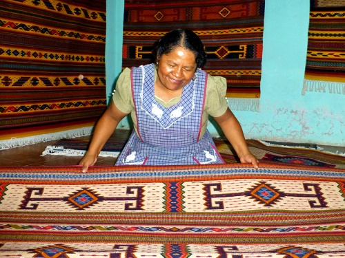 Maria Luisa Mendoza, wife of weaver Fidel Cruz Lazo, displaying their wares in their taller in Teotitlán del Valle.