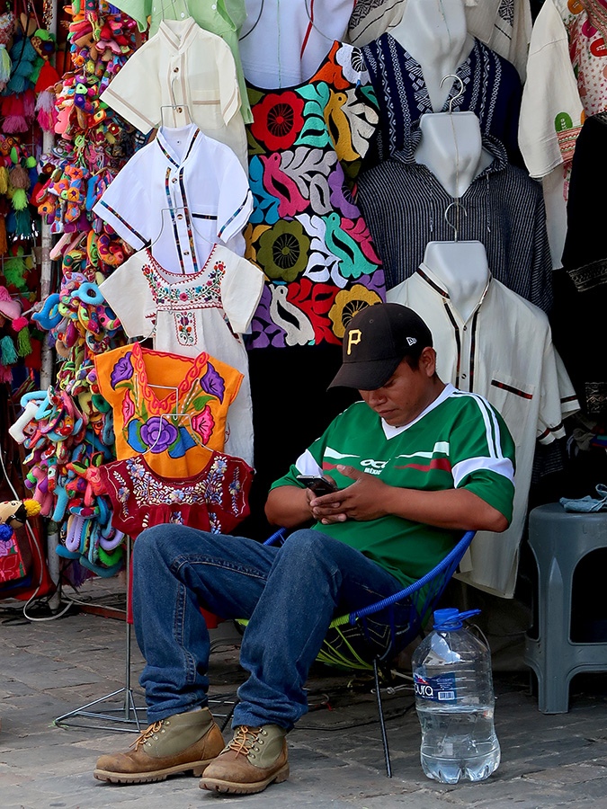 Young man in Mexico soccer jersey sitting